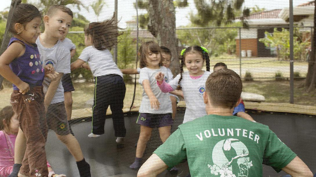 Childacre volunteer plays a game on the trampoline with the children in Costa Rica.